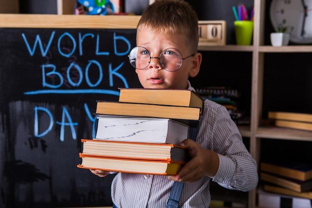 Porträt des niedlichen kleinen jungen, der buch im klassenzimmer hält. glücklicher internationaler weltbuchtag.
