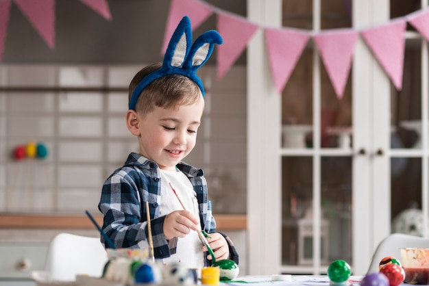Porträt des niedlichen kleinen jungen, der eier für ostern malt