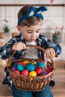 Porträt des niedlichen kleinen jungen, der einen eierkorb hält