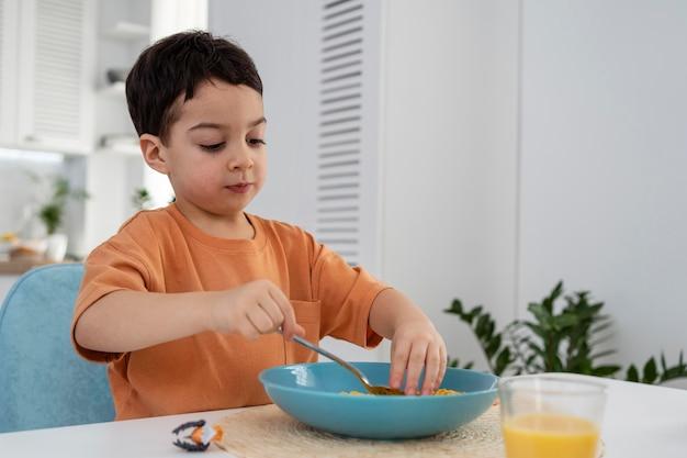 Porträt des niedlichen kleinen jungen, der frühstück hat