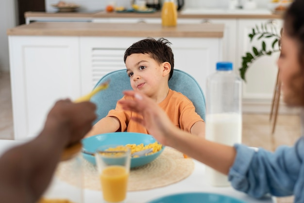 Porträt des niedlichen kleinen jungen, der frühstück mit den eltern hat