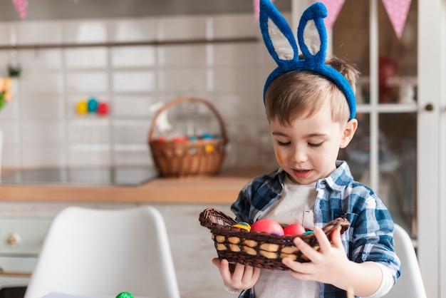 Porträt des niedlichen kleinen jungen, der gemalte eier hält