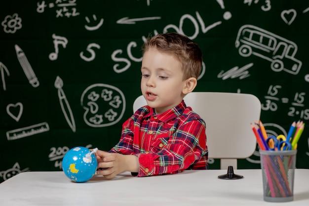 Porträt des niedlichen kleinen jungen, der in händen kleinen globus auf tafelhintergrund hält. fertig für die schule. zurück zur schule.
