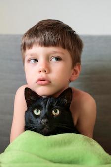 Porträt des niedlichen kleinen jungen, der mit seiner katze aufwirft