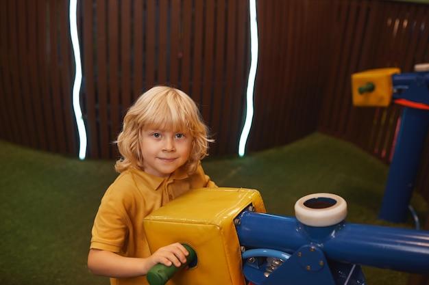 Porträt des niedlichen kleinen jungen, der seine freizeit im unterhaltungspark verbringt