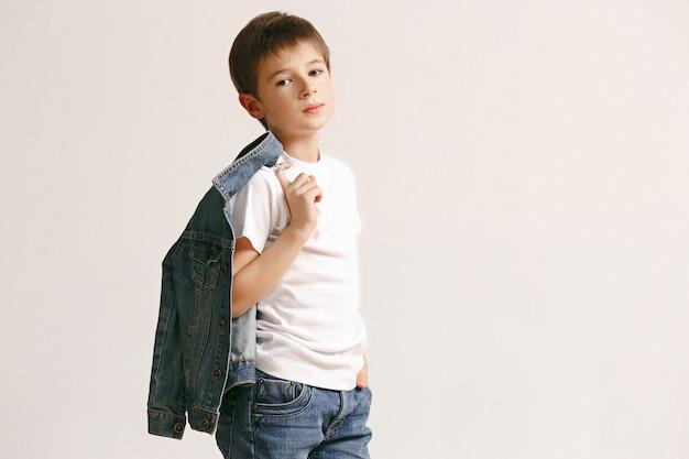 Porträt des niedlichen kleinen jungen in der stilvollen jeanskleidung, die kamera gegen weiße studiowand betrachtet. kindermode-konzept