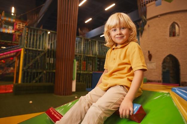 Porträt des niedlichen kleinen jungen mit blondem haar, das vorne beim spielen im unterhaltungspark schaut