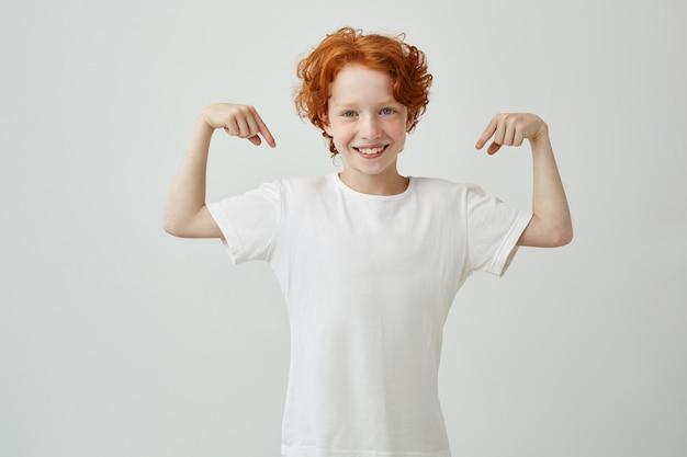 Porträt des niedlichen kleinen jungen mit ingwerhaar, der mit den fingern beider hände auf weißem t-shirt zeigt und lächelt