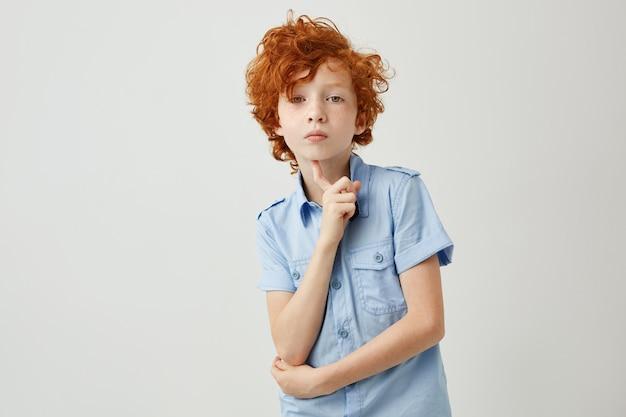 Porträt des niedlichen kleinen jungen mit ingwerhaar und sommersprossen, die mit interesse schauen.