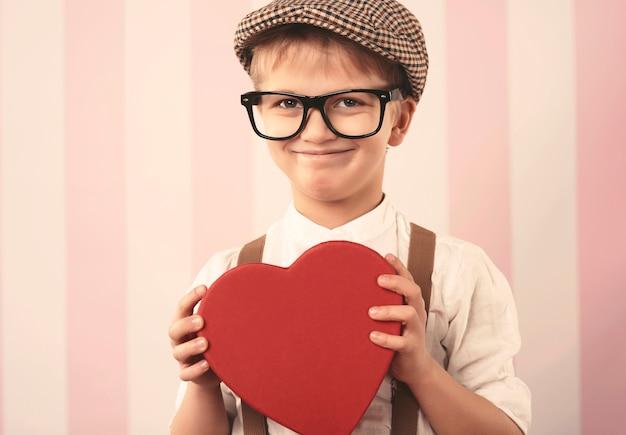 Porträt des niedlichen kleinen jungen mit valentinsgeschenk