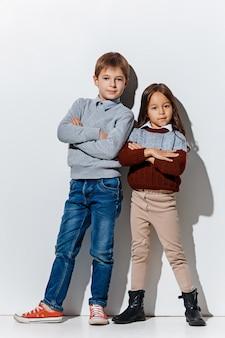 Porträt des niedlichen kleinen jungen und des mädchens in der stilvollen jeanskleidung, die kamera im studio betrachtet