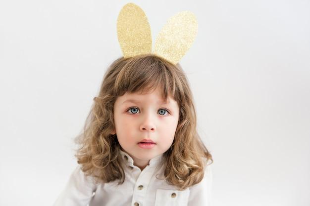 Porträt des niedlichen kleinen kindermädchens, das goldene hasenohren trägt. osterfeier.