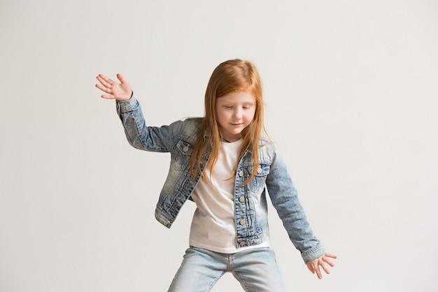 Porträt des niedlichen kleinen kindes in der stilvollen jeanskleidung, die kamera betrachtet und lächelt