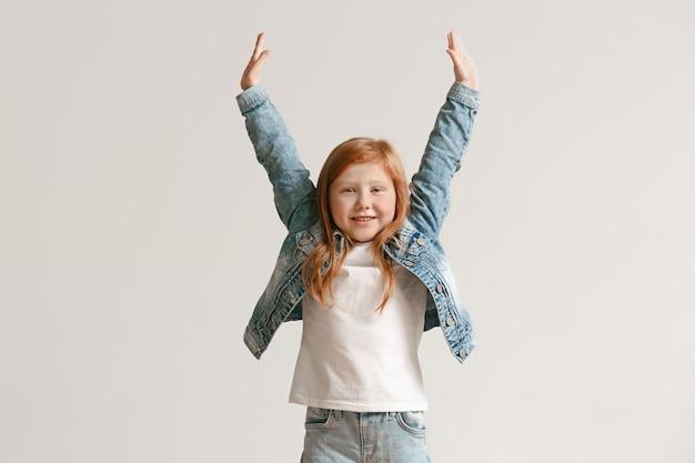 Porträt des niedlichen kleinen kindes in voller länge in stilvollen jeanskleidern lächelnd