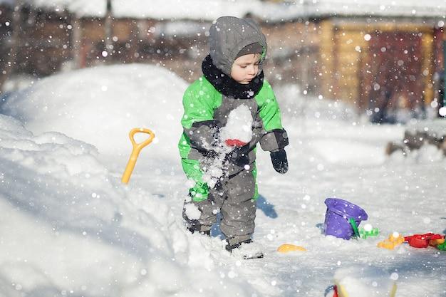 Porträt des niedlichen kleinen kleinkindes, das auf schnee sitzt und mit seinem gelben traktorspielzeug im park spielt. kind spielt im freien. glücklicher junge mit konstruktionsspielzeug. lifestyle-konzept.