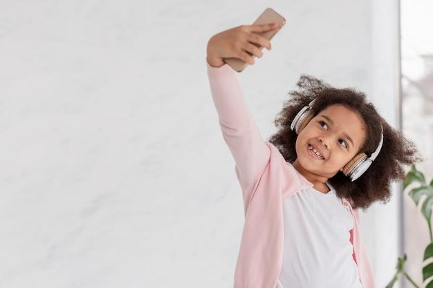 Porträt des niedlichen kleinen mädchens, das ein selfie nimmt
