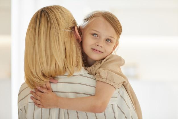 Porträt des niedlichen kleinen mädchens, das glückliche mutter mit liebe umarmt, während in ihren armen lächelnd sitzt