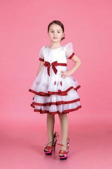 Porträt des niedlichen kleinen mädchens, das im weißen kleid in den schuhen der mutter auf dem rosa im studio steht