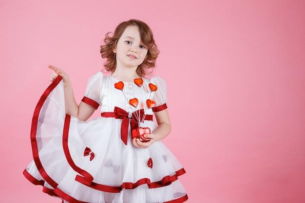 Porträt des niedlichen kleinen mädchens, das im weißen kleid mit donuts oder glasherz auf dem rosa im studio steht