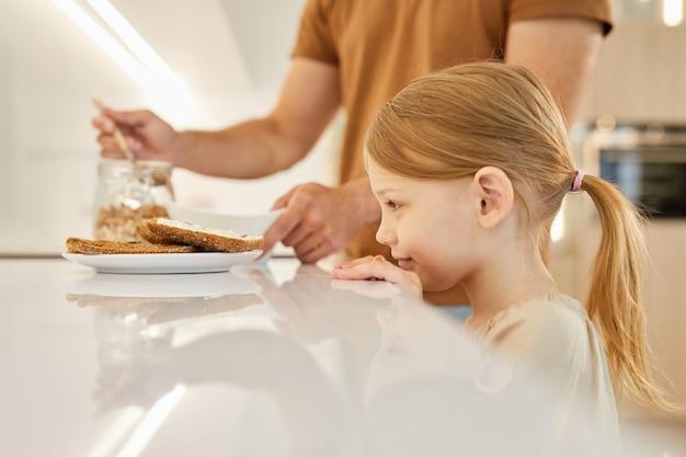 Porträt des niedlichen kleinen mädchens, das leckere sandwiches beim warten auf frühstück in der küche betrachtet