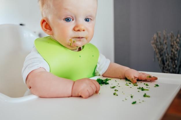 Porträt des niedlichen kleinen mädchens, das nach dem füttern unordentlich sitzt