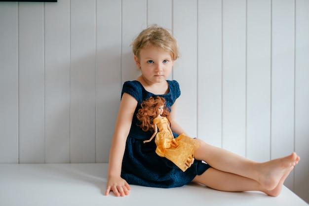 Porträt des niedlichen kleinen mädchens hält ihren schönen barbie, sitzt im hellen babyzimmer