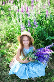 Porträt des niedlichen kleinen mädchens im hut im feld der lupinen. mädchen, das einen blumenstrauß von lila blumen hält