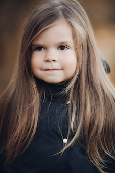 Porträt des niedlichen kleinen mädchens mit langen haaren und haselnussbraunen augen mittlerer nahaufnahme. entzückendes gesicht des weiblichen kindes mit perfekter haut und natürlicher schönheit, die ruhegefühl hat