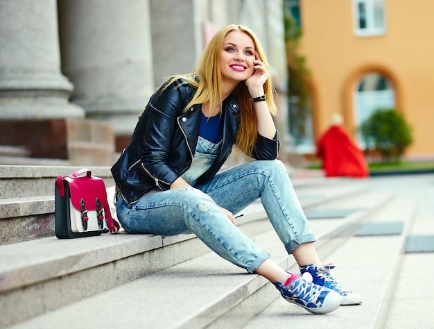 Porträt des niedlichen lustigen modernen sexy städtischen jungen stilvollen lächelnden frauenmädchenmodells im hellen modernen stoff draußen, der in der stadt in jeans mit rosa tasche sitzt
