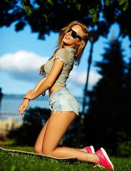 Porträt des niedlichen lustigen sexy jungen stilvollen lächelnden frauenmädchenmodells in hellem modernem stoff mit perfektem sonnengebadetem körper draußen im park in jeansshorts mit skateboard in gläsern