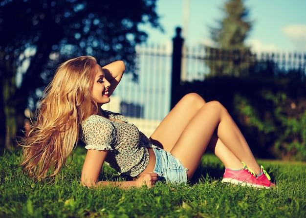 Porträt des niedlichen lustigen sexy jungen stilvollen lächelnden frauenmädchenmodells in hellem modernem stoff mit perfektem sonnengebadetem körper im freien liegend im park in jeansshorts, die gesundes starkes haar in der hand halten