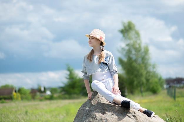 Porträt des niedlichen mädchenkindkindes, der auf großem stein auf blauem himmel sitzt