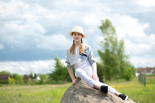 Porträt des niedlichen mädchens, das auf großem stein auf blauem himmel sitzt