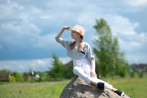Porträt des niedlichen mädchens, das auf stein sitzt und ihre hand zu den augen hob, die in die ferne starren