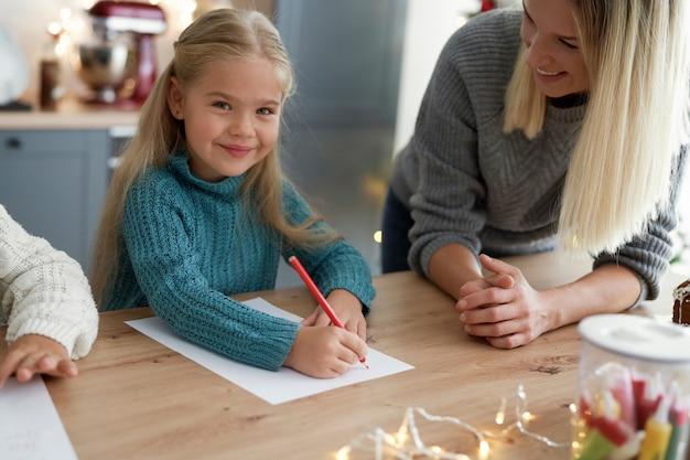 Porträt des niedlichen mädchens, das brief an den weihnachtsmann schreibt