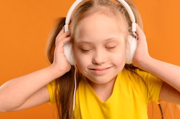 Porträt des niedlichen mädchens, das musik hört