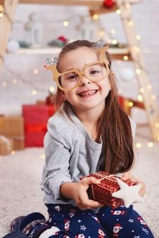 Porträt des niedlichen mädchens, das weihnachtsgeschenk hält