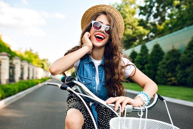 Porträt des niedlichen mädchens mit dem langen lockigen haar im hut, der ein fahrrad auf straße fährt. sie trägt einen langen rock, ein wams und eine blaue sonnenbrille. sie lächelt in die kamera.