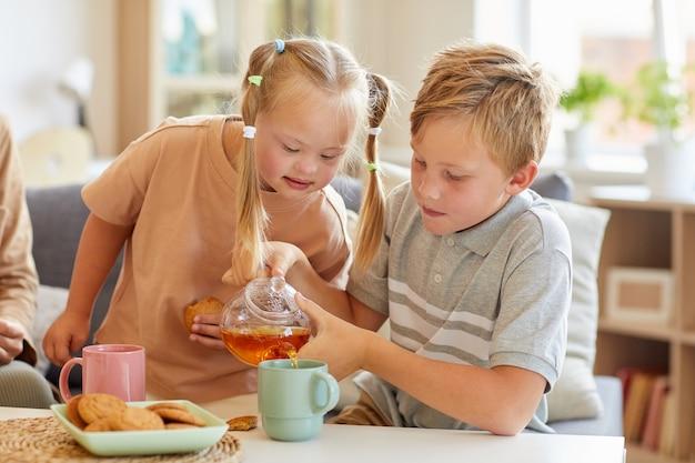 Porträt des niedlichen mädchens mit down-syndrom, das tee mit familie genießt, während im sonnenbeschienenen wohnzimmer zu hause sitzen, raum kopieren
