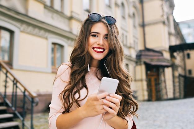 Porträt des niedlichen mädchens mit langem lockigem haar und telefon in den händen, die in der stadt auf gebäudehintergrund lächeln