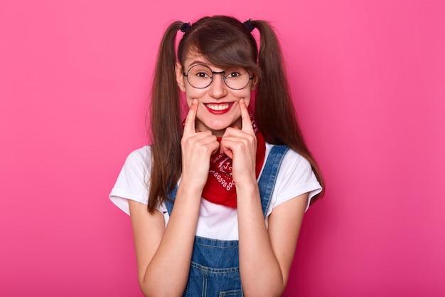 Porträt des niedlichen mädchens mit langen haaren, trägt t-shirt, jeansoverall und halstuch am hals. charmantes schulmädchen mit zahnigem lächeln, hält die finger auf der wange, posiert im studio isoliert über pink
