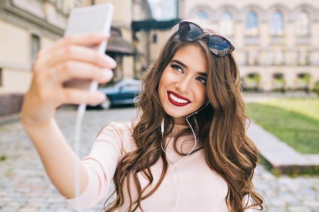 Porträt des niedlichen mädchens mit langen haaren und schneeweißem lächeln, das selfie auf straße in der stadt macht. sie trägt weinige lippen und lächelt.