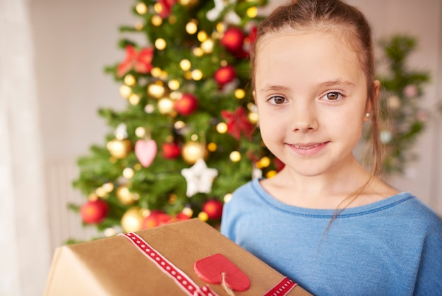 Porträt des niedlichen mädchens mit weihnachtsgeschenk