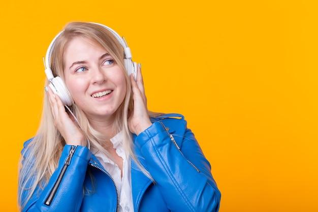 Porträt des niedlichen positiven jungen blonden mädchens, das lieblingsmusik in den kopfhörern in blau hört