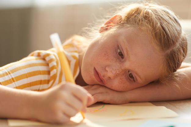 Porträt des niedlichen rothaarigen mädchens, das bilder zeichnet, während sie ihren kopf im sonnenlicht auf tisch legt