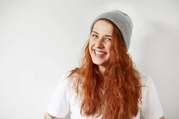 Porträt des niedlichen rothaarigen mädchens, das graue wintermütze und lächelndes weißes t-shirt trägt