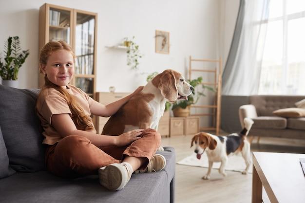 Porträt des niedlichen rothaarigen mädchens, das mit hunden spielt, die zu hause mit gekreuzten beinen auf dem sofa sitzen