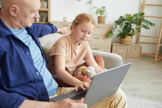 Porträt des niedlichen rothaarigen mädchens unter verwendung des laptops beim genießen der zeit mit großvater im gemütlichen innenraum