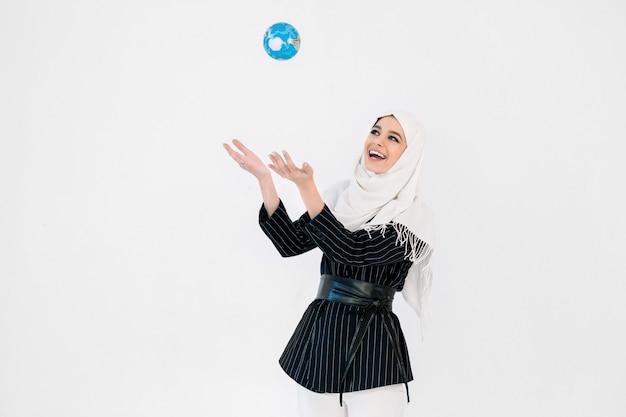 Porträt des niedlichen schönen asiatischen muslimischen mädchens, das hijab trägt und lächelt, während er kleine erdkugel wirft