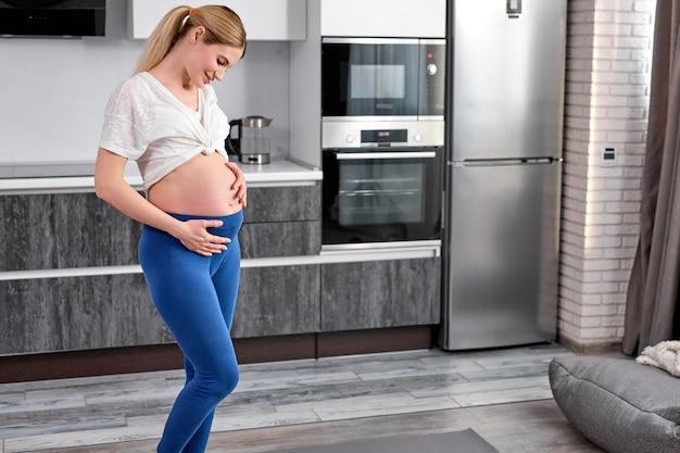 Porträt des niedlichen schwangeren weiblichen blicks auf bauchbauch mit liebesstreicheln